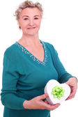 Smiling granny with gift in hand over a white — Stock Photo