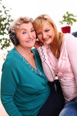 Granny and granddaughter listening music — Stockfoto