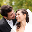 Beautiful bride and happy groom in autumn park — Stockfoto
