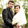 Beautiful bride and happy groom in autumn park — Stock Photo