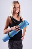 спортивный и привлекательная блондинка с голубой мат — Стоковое фото