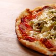 Image of fresh italian pizza on a wooden suface — Foto de Stock