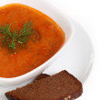 Image of bowl of hot red soup and piece of bread - Stock Photo