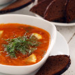 Bowl of red soup and black bread on white table — Stock Photo #18266535