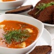 Bowl of red soup and black bread on white table — Stock Photo #18266551