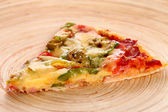 Slice of tasty italian pizza on a bamboo plate — Stock Photo