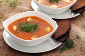 Image of bowls of hot red soup served with bread — Stock Photo