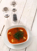 Bowl of hot red soup served on wooden table — Stock Photo