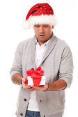 Handsome man in christmas hat surprised — Stock Photo