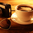 Coffee cup with retro photocamera — Stock Photo
