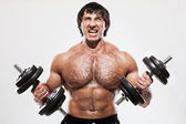 Muscular guy working out with dumbbells — Stock Photo