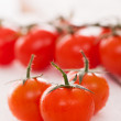 Fresh cherry tomatoes on a white surface - Stock fotografie