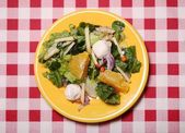 Fresh tasty salad in a plate on a tablecloth — Stock Photo