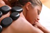 Hermosa mujer disfrutar de spa con piedras — Foto de Stock
