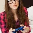 Young woman in casual playing videogame — Stock Photo #25257375