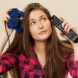 Young woman with joystick and TV console - Stok fotoğraf
