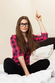 Cute young girl in glasses on the bed — Stock Photo