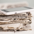 Pile of newspapers with smartphone on it — Stock Photo #25390267