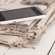 Pile of newspapers with smartphone on it — Stock Photo