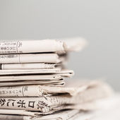 Pile of newspapers on a white table — Stock Photo
