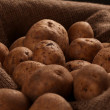 Rustic unpeeled potatoes on a desks - Stock Photo
