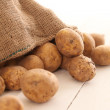 Rustic unpeeled potatoes on a table — Stock Photo