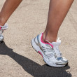Woman legs in sneakers on asphalt — Stock Photo