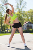 Happy young woman exercising outdoors — Stock Photo