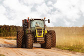 Tractor on a road at countryside near meadows — Stock Photo