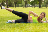 Beautiful young woman exercising on a grass — Stock Photo