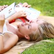 Two girls laying on the ground and reading magazines — Stock Photo #30208275