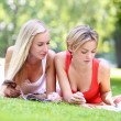 Two girls laying on the ground and reading magazines — Stock Photo