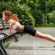 Fitness girl is working out in the park — Стоковая фотография