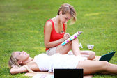 Two girls are chilling at park — Stock Photo
