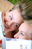 Two girls are hiding behind magazines — Stock Photo