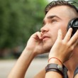 Handsome man sitting in the street with headphones — Stock Photo #30210287