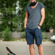 Handsome guy with headphones and skateboard — Stock Photo
