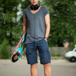 Handsome guy with headphones and skateboard — Foto Stock