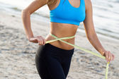 Fitness girl measures her waist — Stock Photo