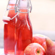 Stock Photo: Bottles with red drinks and some apples