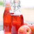 Bottles with red drinks and some apples — Stock Photo