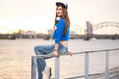 Chica elegante sentado en una barandilla — Foto de Stock