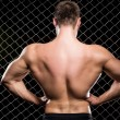 Powerful guy showing his muscles on fence background — Stock Photo