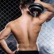 Powerful guy with a dumbbells showing muscles on fence backgroun — Stock Photo