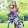 Stock Photo: Beautiful girl with flowers on bike