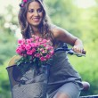 Beautiful girl with flowers on a bike — Stock Photo