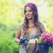 Beautiful girl with flowers on a bike — Stock Photo #37176275