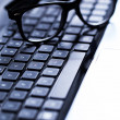 Laptop keyboard with glasses — Stock Photo