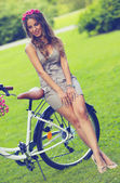 Beautiful girl with flowers on a bike — Foto Stock