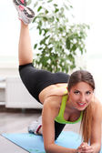 Beautiful woman working out at home — Stock Photo